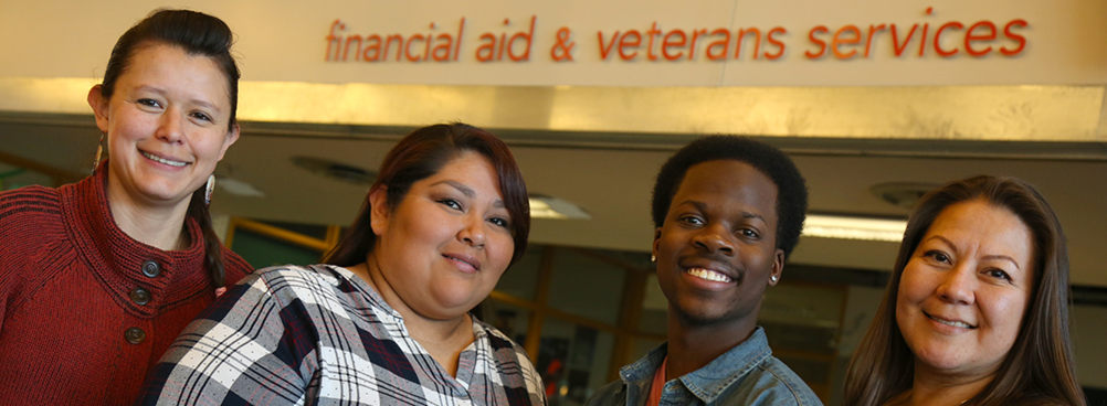 Picture of students in front of Financial Aid & Veterans Services sign